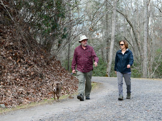 Jess and Joy Benton walk their dog, Gretta, on Bent Creek Road at the North Carolina Arboretum.