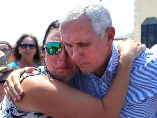 Deidra Cate (left) is comforted by Vice President Mike Pence at the First Baptist Church of Rockport on Thursday, Aug. 31. The vice president and several Cabinet secretaries visited Rockport to reaffirm the federal government's promise of help for victims of Hurricane Harvey. Cate said parents are concerned about the state of local schools and want them operating as soon as possible.