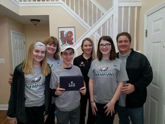 Cole Fitzgerald stands between sisters Maggie, left, and Maeve in their Washington Township home. In the back row, mother Keren and father Bill flank Spare Key staffer Mary Serie.