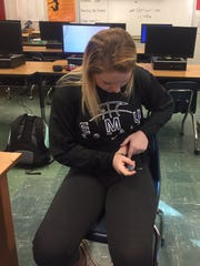 Macey Snyder injects insulin into her stomach Wednesday