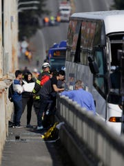 People with bandaged arms stand next to a bus involved