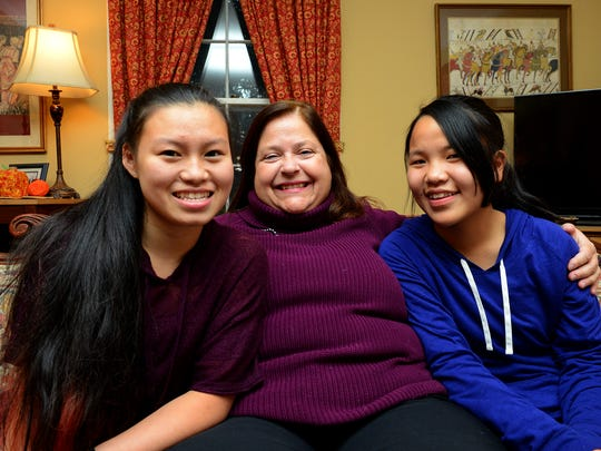 Lansing State Journal  reporter Kathleen Lavey sits for a portrait with her two daughters Julianna, 15, left, and Ella, 13, Thursday, November 20,2015 at their home in East Lansing. Lavey adopted Juliana from China 15 years ago this Thanksgiving. She adopted Ella from China two years later.