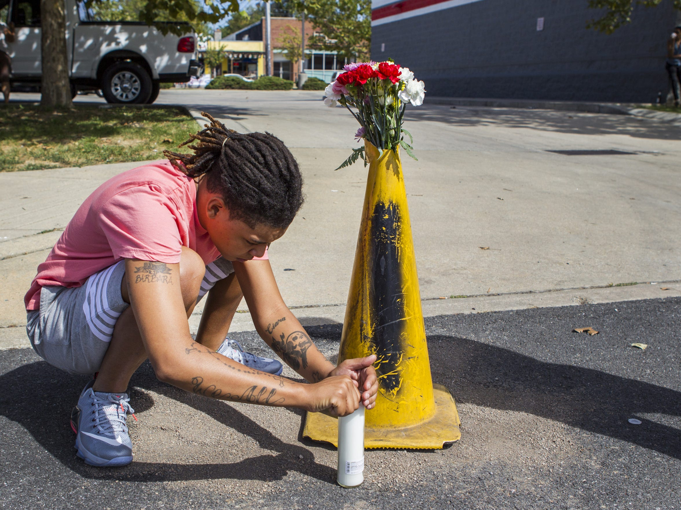 A woman who would not give her name, but described herself as a family member of Jeremy McDole, lights a candle at a makeshift memorial the morning after his death. McDole was shot and killed by members of the Wilmington Police Department near the corner of Tulip and Scott Streets in Wilmington on Sept. 23, 2015.