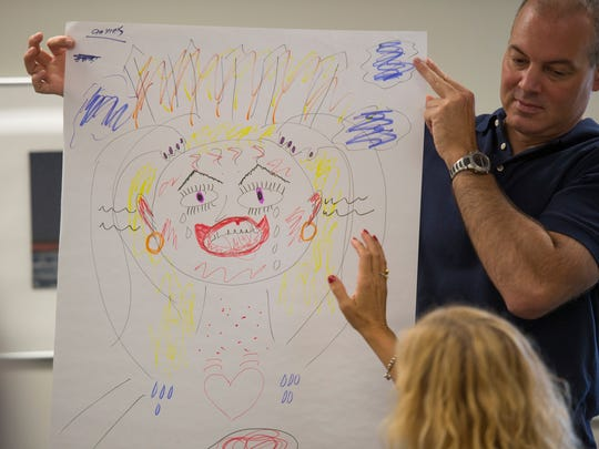 Course Instructor John Noullet holds up a drawing where participants were asked to draw what anxiety looks like during a Mental Health First Aid training at the Lebanon County Mental Health building on Friday, Sept. 16, 2016.