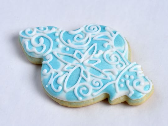 To fashion the elaborate design on this Tot's Treats cookie, an image is projected onto the cookie, then traced in icing.