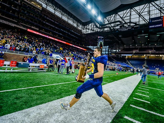 Pewamo-Westphalia senior offensive lineman Dominic Spitzley prances toward the Pewamo-Westphalia stands carrying the Pirates Division 7 state championship trophy Saturday November 26, 2016 at Ford Field in Detroit.