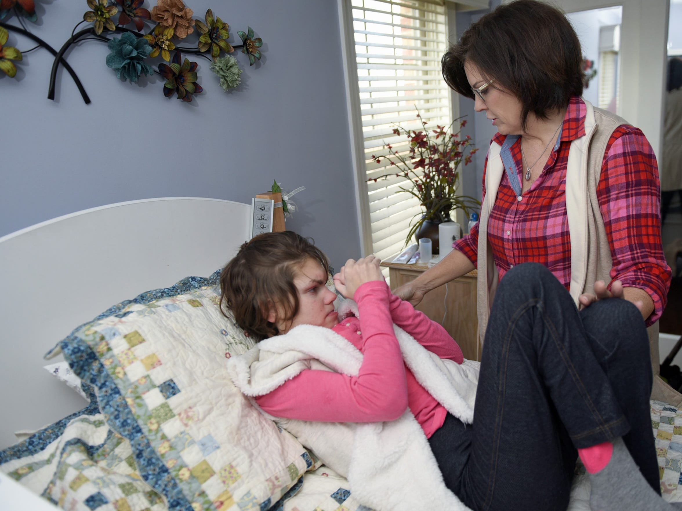 Karen Diller helps her daughter, Karly, 20, out of bed on Friday, February 20, 2017 at their Chambersburg area home. Karly was born with a rare X-linked genetic disorder that causes seizures called CDKL 5 and is on a clinical trial of a drug that uses marijuana.