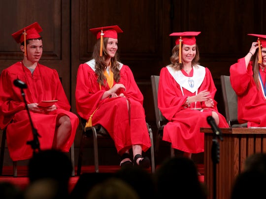 Four of Christ Academy's graduates sit onstage as they listen to the valedictorian give his address Friday, May 19, 2017, at Grace Church.