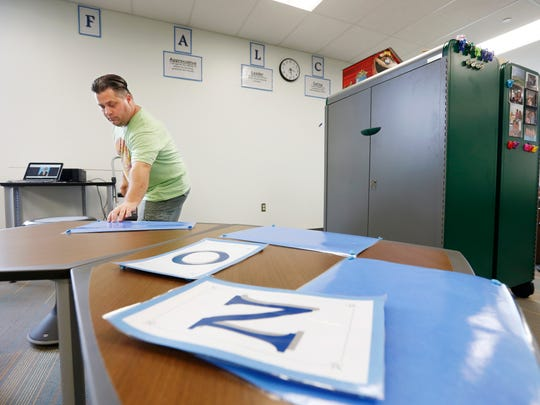 Teacher Troy Kuchta gets his classroom ready at the