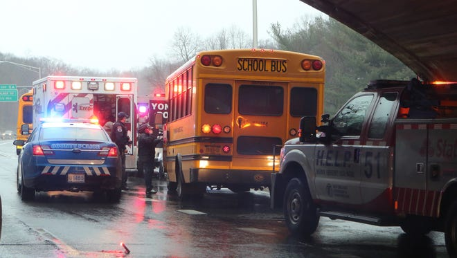 Westchester County police and Empress ambulance personnel respond after a mini school bus got wedged under the Yonkers Avenue overpass on the Saw Mill River Parkway in Yonkers on April 6, 2017.