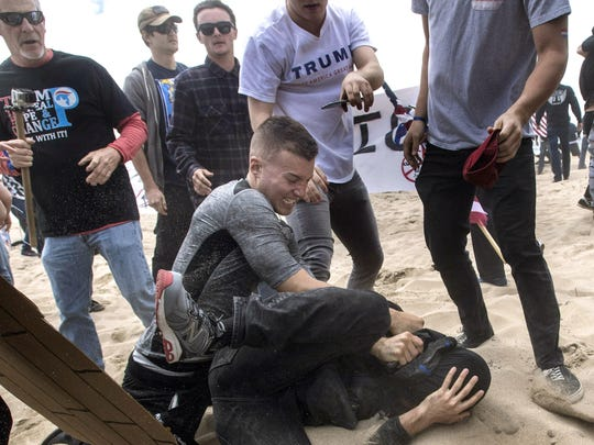 A supporter of President Donald Trump, center, clashes with an anti-Trump protester, bottom center, in Huntington Beach, Calif., on Saturday, March 25, 2017.