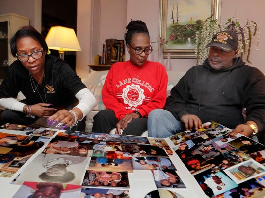 Sister Carmen Adams (from left), mother Gwen Adams and father Johnnie Adams look over family photos of brother and son Corey Adams who suffered from PTSD and was found dead 18 days after going missing. Because of Adams' case, state legislators are working to get a Green Alert for missing and vulnerable veterans just like the Amber and Silver alerts. The state Senate passed the bill this week and the Assembly will take it up next month.