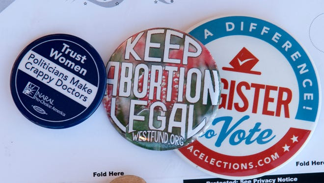 "Buttons supporting abortion and a women's right to choose over politicians adorned a table set up to register voters at the ""We Decide"" celebration honoring of abortion providers held at the Whole Women's Health clinic on Lohman Ave. 9/29/16"
