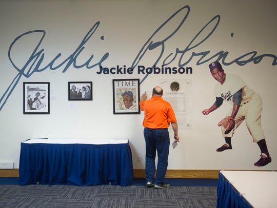 Laurence Reisman, community editor for TCPalm, studies a Jackie Robinson display Tuesday, Oct. 10, 2017, at Historic Dodgertown in Vero Beach. Since the Los Angeles Dodgers ended spring training activity at the Vero Beach complex in 2008, many rooms have turned into tributes to the team, featuring magazine covers, photos, baseball bats and more.
