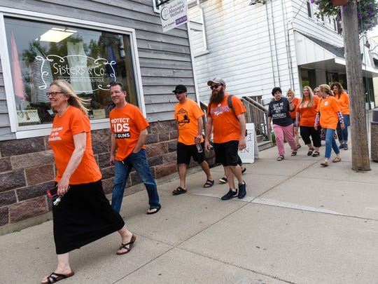 """Residents promoting an """"orange out"""" in St. Joseph to speak out against gun violence walk down Minnesota Street Thursday, May 24."""