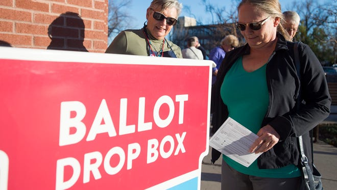 Election volunteer Ann Green greets Jane Slusarski-Harris as she drops off her ballot in a drop box at the Larimer County Courthouse Wednesday in Fort Collins.