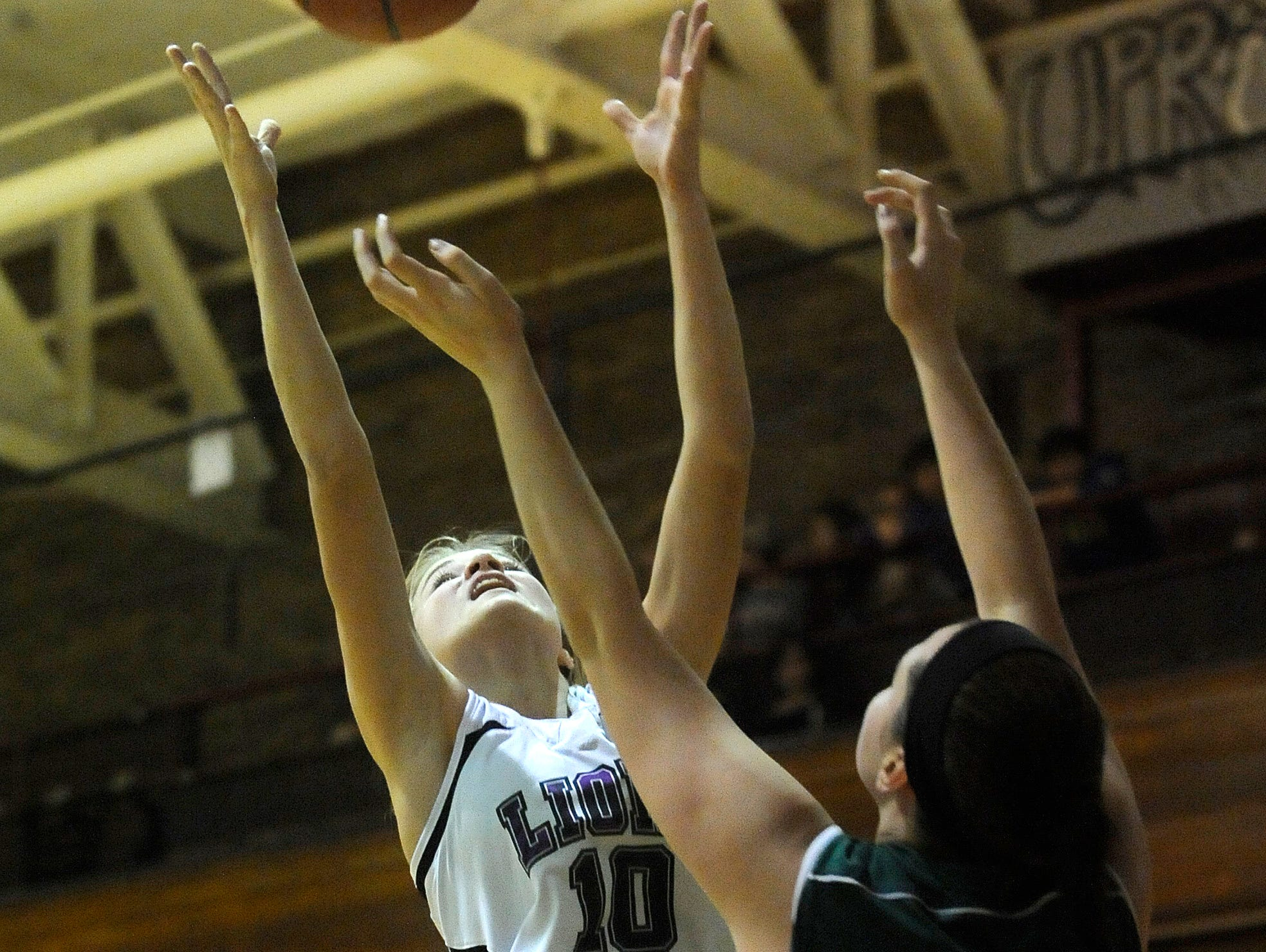 Granville Christian's Payton Hartshorn pulls down a rebound over Northridge's Kendra Martin. The Lions defeated the Vikings 38-27 on Friday, Nov. 20, 2015, at the Fifth Street Gym in Newark.