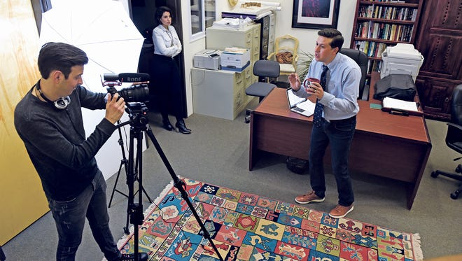 """In a Feb. 9, 2017 photo, Henry Valdez plays Brad, Marina Rossi who plays Andrea and Michael Estrada plays Joey, cast members of 'Bad Broker' film their """"pitch"""" video for Indiegogo in Santa Fe, N.M., to solicit $5,000 in open source funding in the real estate office they use as a set for their web series."""