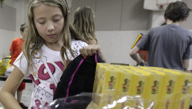 Volunteer Eva Selig, from the Boys & Girls Clubs of the Fox Valley, fills a backpack Aug. 5 as part of the Backpacks for Kids campaign at Post-Crescent Media.