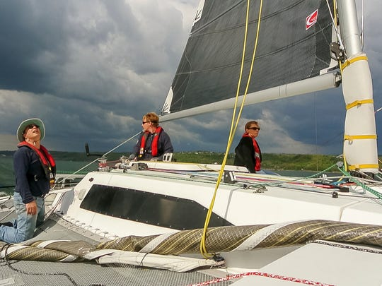 From left, boat owner Richard Stephens, Keith Rice and Melissa Grey sail Stephens' 28-foot Corsair trimaran Trevelyn during a May race organized by the Cruising Fleet at the Ithaca Yacht Club on Cayuga Lake.