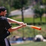 Xavier basketball's Sean O'Mara swings the bat during the team's second annual softball game Thursday.