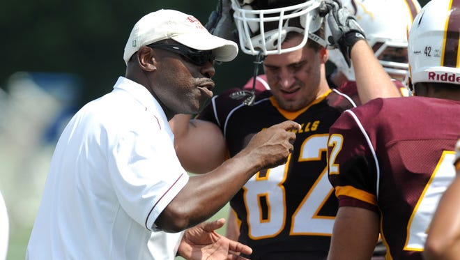 Salisbury's Head Coach Sherman Wood talks with his defensive line during a timeout in a 2011 game against Ithica Collage.