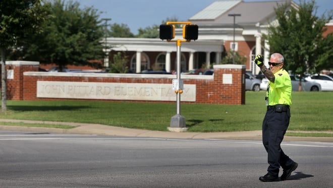 A crossing guard handles traffic in front John Pittard Elementary School in 2014.