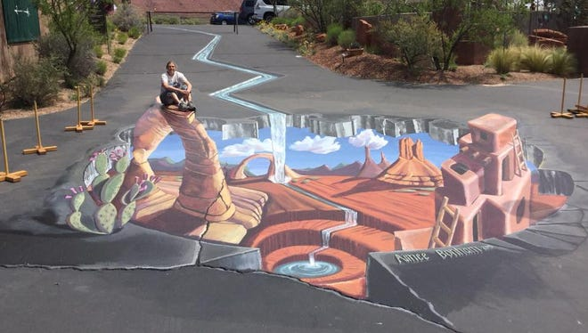 Aimee Stephens Bonham poses in a photo of her recently completed permanent three-dimensional street painting in Kayenta.