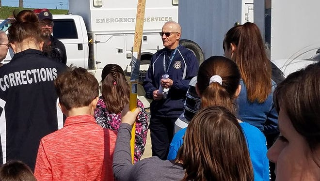 Jake Crider (center), emergency management coordinator and assistant director, talks to participants at Take Our Daughters and Sons to Work Day on Thursday, April 26. The event gave more than 70 children of county employees the chance to learn more about jobs within the county, and why each one is important.
