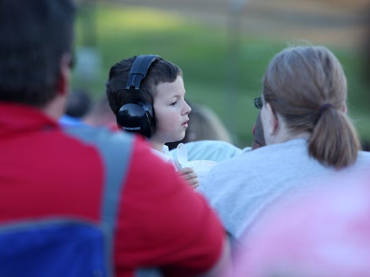 A young race fan wears his ear muffs and enjoys some ice cream during racing at Lincoln Park Speedway in Putnamville, July 1, 2016.