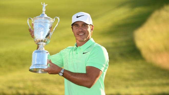 Former Florida State golfer Brooks Koepka poses with the trophy after winning the U.S. Open golf tournament at Erin Hills.