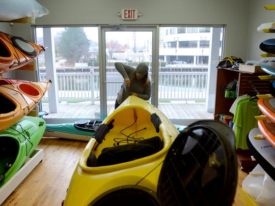 Missy Campau works on a kayak Monday, Dec. 7, at her new store, Missy's Kayak Connection, in Port Huron along the Black River.