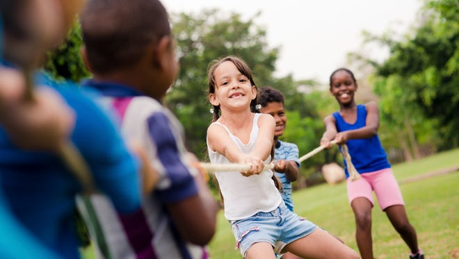 """""""Children and recreation, group of happy multiethnic school kids playing tug-of-war with rope in city park. Summer camp fun"""""""