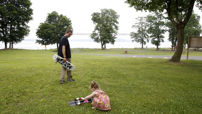 Mike Ehlers, 43, of Stony Point has been leading an effort to build a skate park for local youths. Ehlers and his 23-month-old daughter Annabelle, are photographed at the skate park's future location, July 8, 2015 in Stony Point.