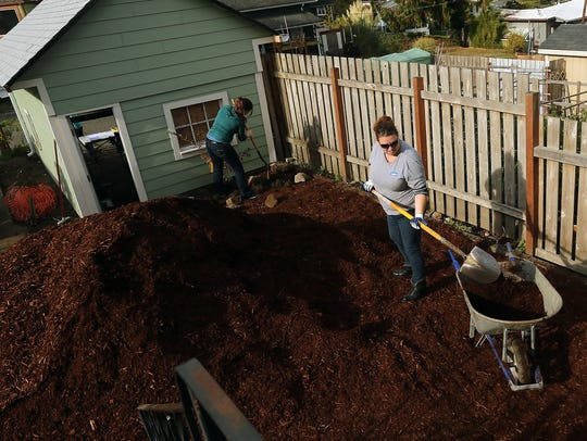 Leslie Breckel, right, a volunteer from Lowe's Home Improvement, fills a wheelbarrow with bark as she and fellow volunteers work on the landscaping of a Community Frameworks home on Highland Avenue in Bremerton.