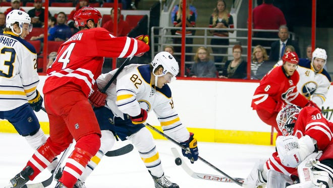 Carolina Hurricanes goalie Cam Ward and defensemen Jay Harrison stop a shot by the Buffalo Sabres forward Marcus Foligno on Friday.