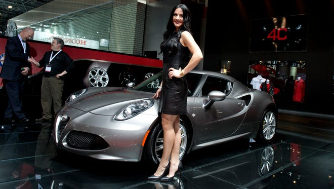 Product Specialist Chelsea Duda of Rochester Hills, Mich., stands next to the Alfa Romeo 4C on displayat New York International Auto Show at the Jacob K. Javits Convention Center in New York.