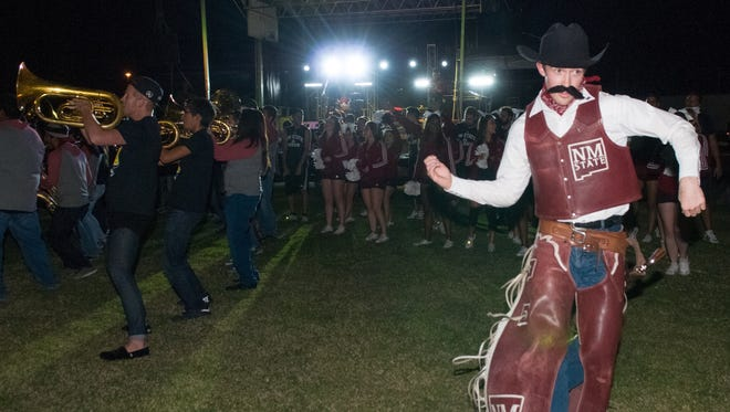 Pistol Pete dances as the band preforms on Friday during the annual NMSU Aggie Bonfire at the student tailgating lot.