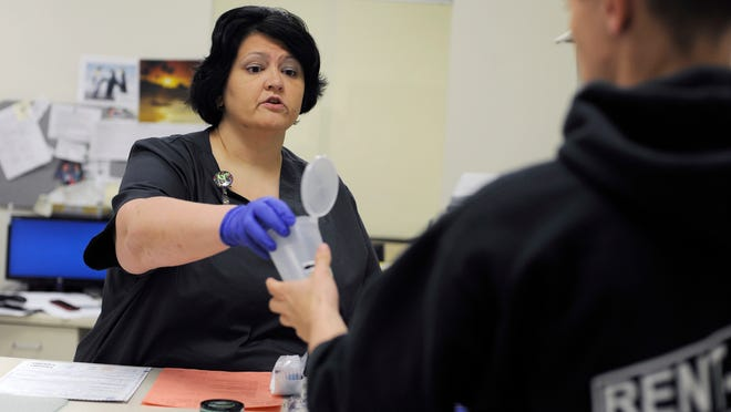 Adena Occupational Health Coordinator of Alcohol and Drug Testing Melissa Davis hands an empty cup for a urine sample to a patient needing to take a drug test.