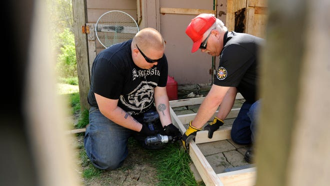 Franklin Township volunteer firefighter Justin Richmond works with Mark Adkins, of 1-800-BoardUp, to install a wheelchair ramp for a young man who was in a car crash and will be in a wheelchair for at least a year.