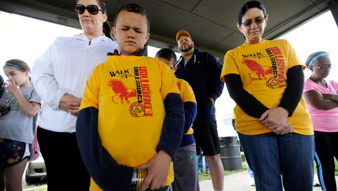 Aaron Manazer, 8, bows his head to pray with his family and others participating in the Ross County Christian Academy fundraising walk at Yoctangee Park on Saturday.