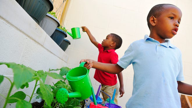 Michael Holt, left, and Ricky Robinson water the garden in the pre-K program at Casa Azafrán in Nashville on May 7.