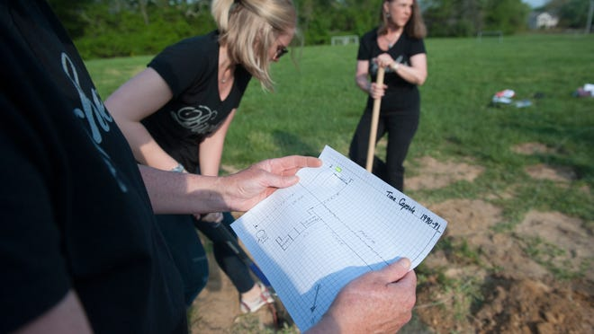 Bettiann Young reads a map as Kim Maffet and Lori Mazzeo from Birches Elementary School in Turnersville dig up a part of the schoolyard in search of a time capsule that Bettiann Young's 3rd-grade class buried 25 years ago. Tuesday, May 12, 2015.