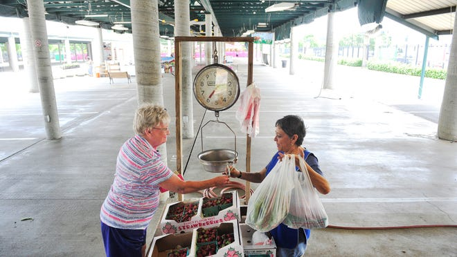 Charliene Sanders buys greens and strawberries from Patricia Muniz last week at the Smiley's Farm booth at the Nashville Farmers' Market.