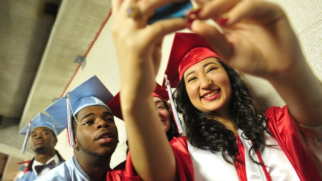 "Geraldine Hernandez, right, takes a picture with friends Leonard Williams, left, and Micaela Herrera as they prepare to graduate from Glencliff High School. ""OK, so this is how it feels to grow up,"" Hernandez says. ""It's kind of overwhelming."""
