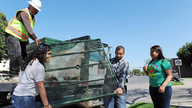 Esmeralda Fletes, 16, of Youth for Change, and CCA community organizer Joel Hernandez carry a new tabletop to a temporary storage area at Acosta Plaza in Salinas on Tuesday.