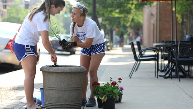 Chillicothe High School 11th-grade cheerleader Reagan Taylor, left, and 10th-grader Athena Stearos work together to plant brightly colored flowers in pots lining the streets of downtown Chillicothe on Wednesday with other members of the cheerleading and volleyball teams.