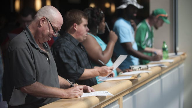 Job seekers fill out applications during Gloucester Premium outlets job fair held at Camden County College. Friday, June 12, 2015.