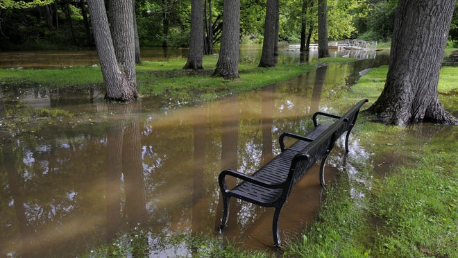 Benches surrounded by water in the partially flooded Riverside Park in DeWitt after the recent heavy rains .