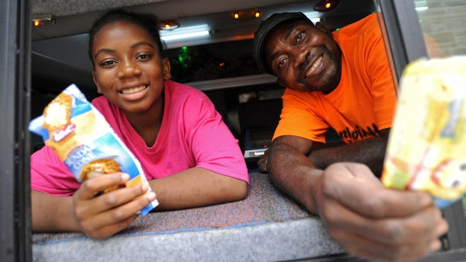 """Anthony Allen and his daughter, Antoinette Allen, 12, smile from their ice cream truck named """"Antoinette's Ice Cream"""" before heading out to sell the sweet treats to hungry locals on Wednesday. The truck offers 24 different types of ice cream treats in addition to other snacks."""